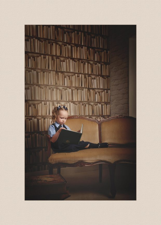 children's photographer glasgowGirl sitting on vintage seat reading a book in school uniform