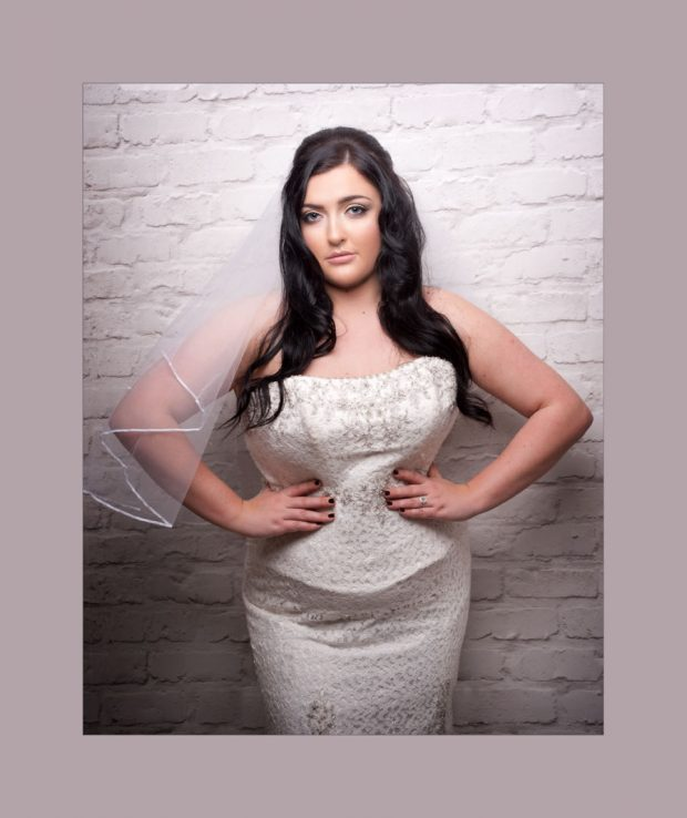 bride standing against a brick wall in a provocative pose