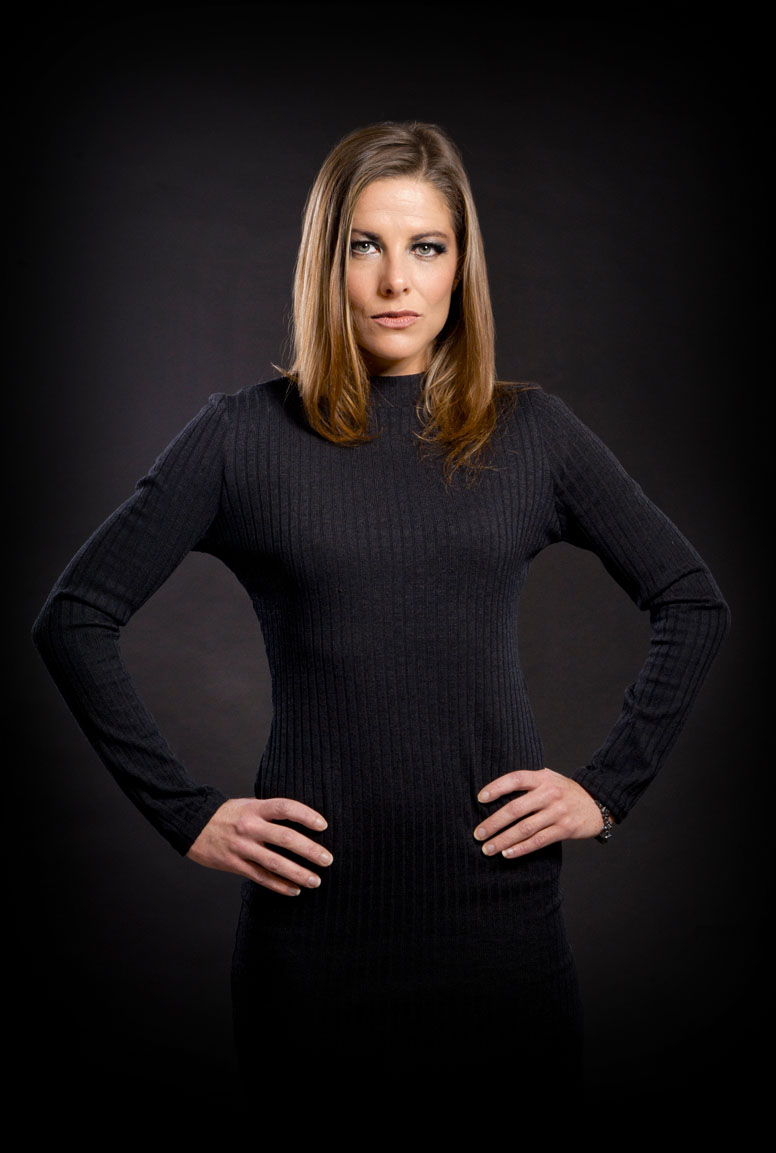 headshot photograph of a business woman in a black dress with hands on hips