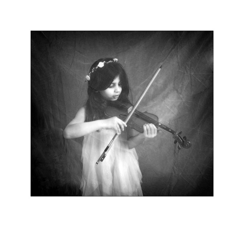 girl with violin in black and white photographed through netting