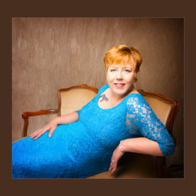 makeover photoshoot lady in blue dress on vinatage sofa