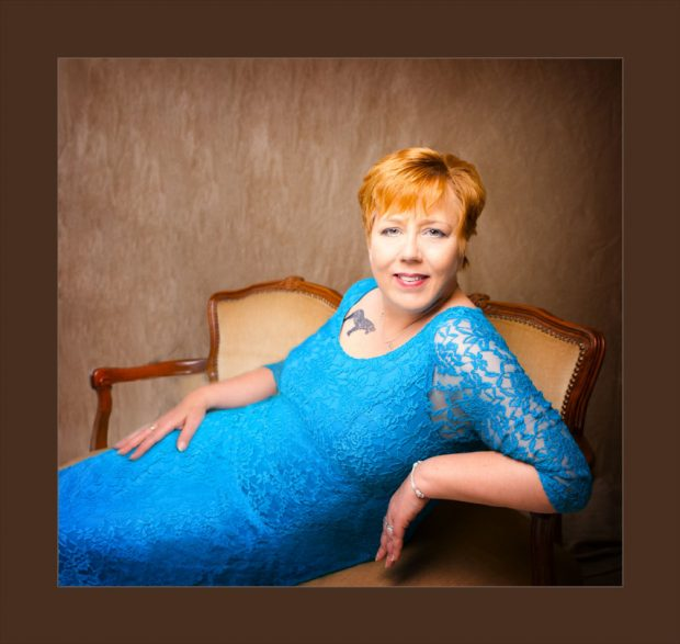 lady in blue lace dress sitting on a vintage couch