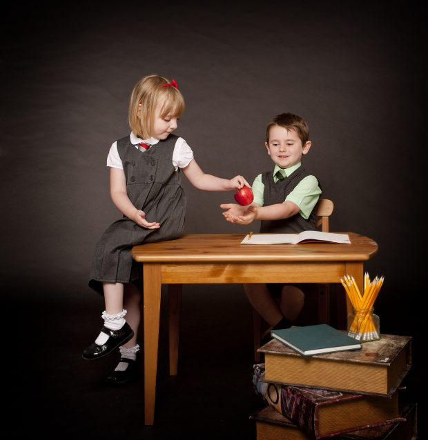girl and boy in school uniform with an apple