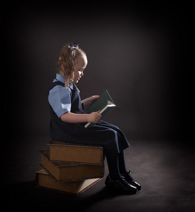 girl in school uniform reading a book on a pile of books
