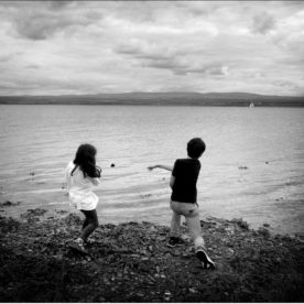 two children skimming stone s on a beach